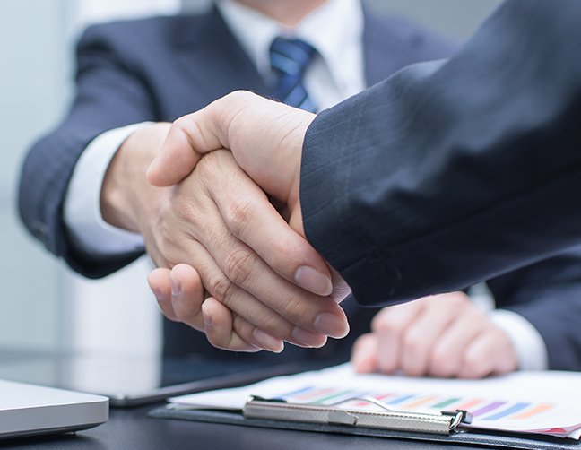 two people shaking hands after buying a business