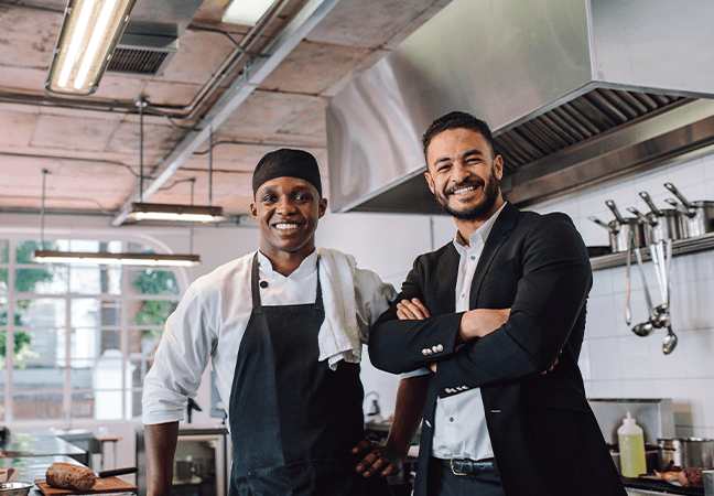 restaurant owner and chef smiling in kitchen