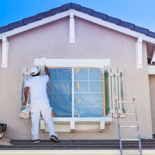 gentleman painting the outside of a house