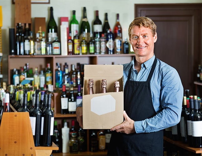 liquor store owner holding box of inventory