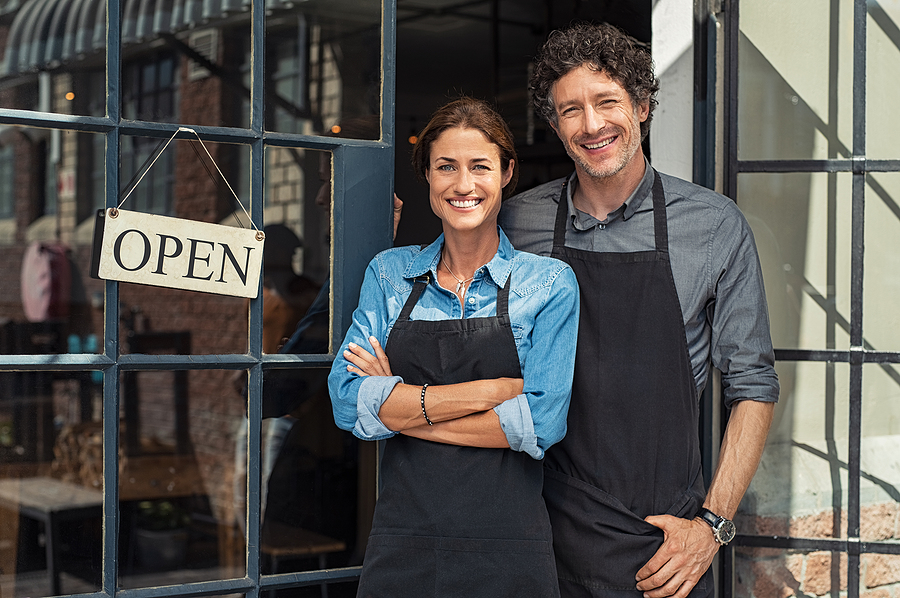 business owners standing in front of shop smiling