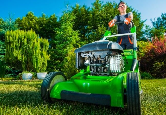 lawn care business owner mowing a customer's yard